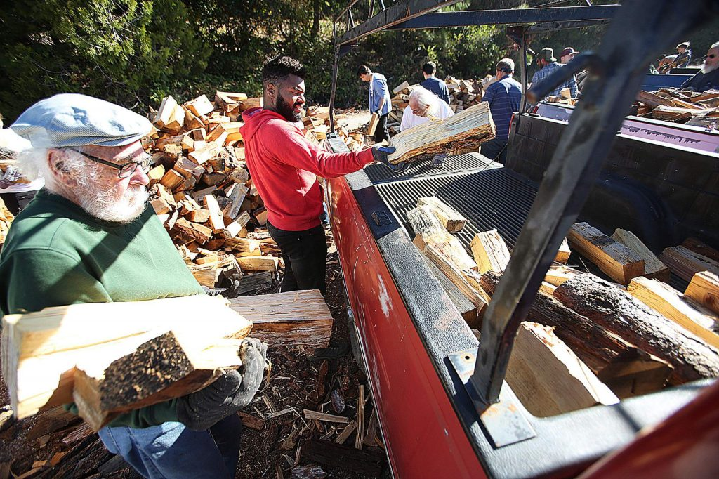 Senior firewood program volunteers Richard Gill, left, and Marcus Willis help to load up the back of a pickup with about a half cord of wood Saturday at the load-up center off Brunswick Road. Qualifying low-income seniors are able to take home a cord and a half of wood.