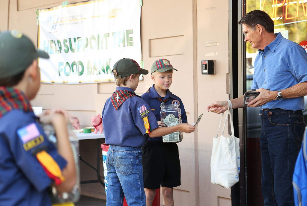 Lukas Hemphill, right, with Cub Scout Pack 23 in Nevada City, and Oscar Thomas collect money from people leaving SPD Market in Nevada City during their Saturday food and donation drive to support the Food Bank of Nevada County.