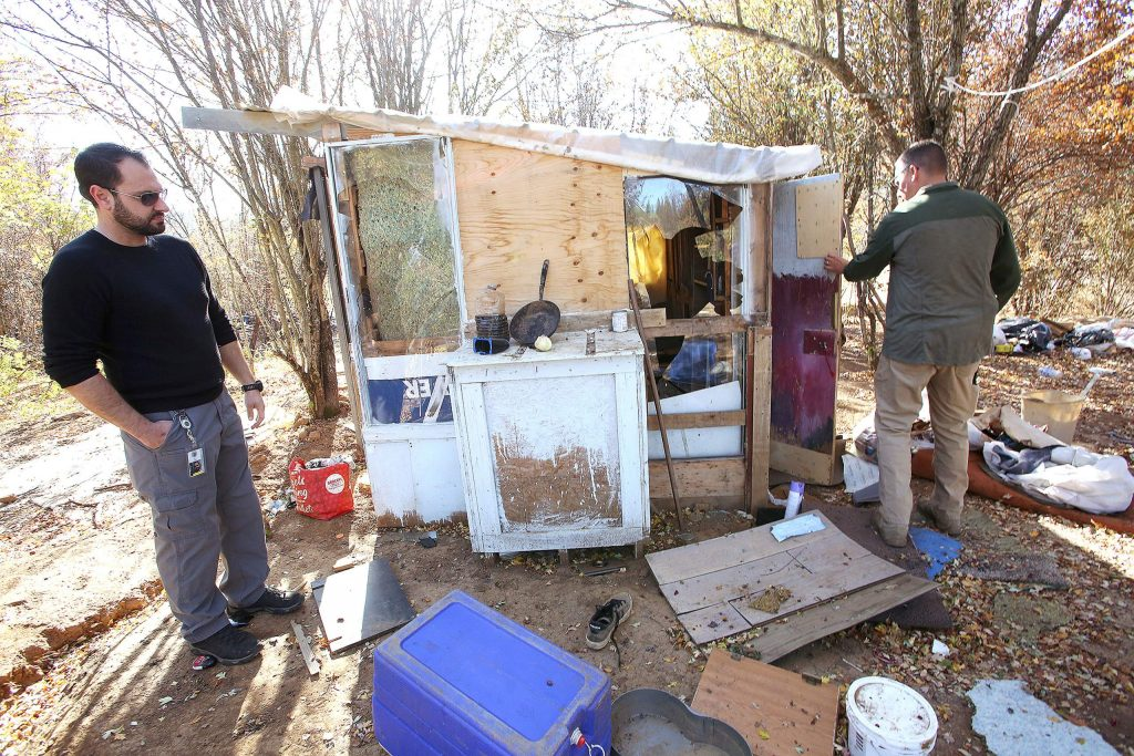 Hospitality House's Joe Naake and Grass Valley Police's Sgt. Brian Blakemore inspect a homeless man's elaborate encampment on the Loma Rica Ranch near the start of the Dorsey Fire.