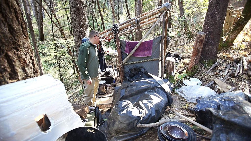 Grass Valley Police Sgt. Brian Blakemore talks to a man who was arrested the night before from this encampment due to lighting a warming fire.
