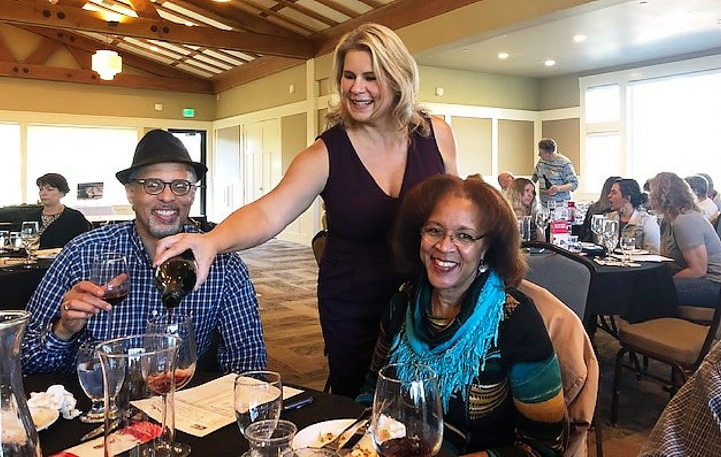 Board member Mondae Hott pours wine for guests Hosea and Hope Bostic at a wine tasting fundraiser for United Way of Nevada County.