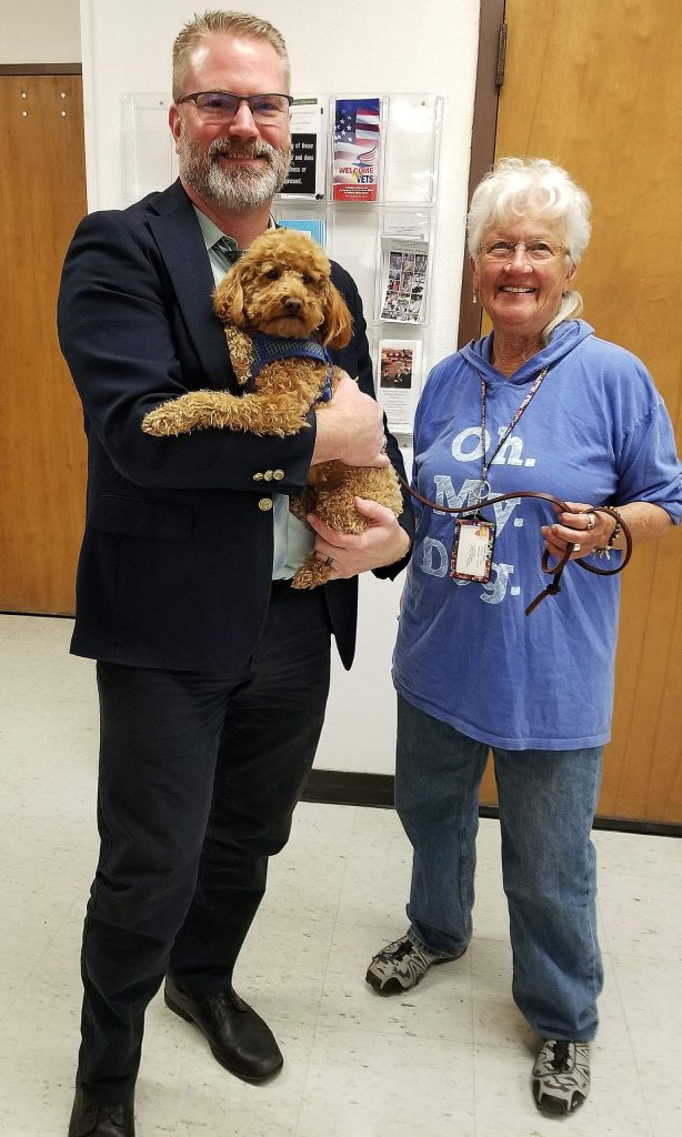 Levi, a miniature poodle, is one of the certified therapy dogs at the Nevada County Courthouse. Levi and owner/handler Jackie Brown share the love with Bailiff Ben Hagel.