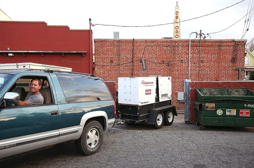 Gary's Place handyman Art Ellis backs an industrial generator into a space behind the downtown Grass Valley bar Tuesday in preparation of a Wednesday and Thursday PG&E power shutdown.