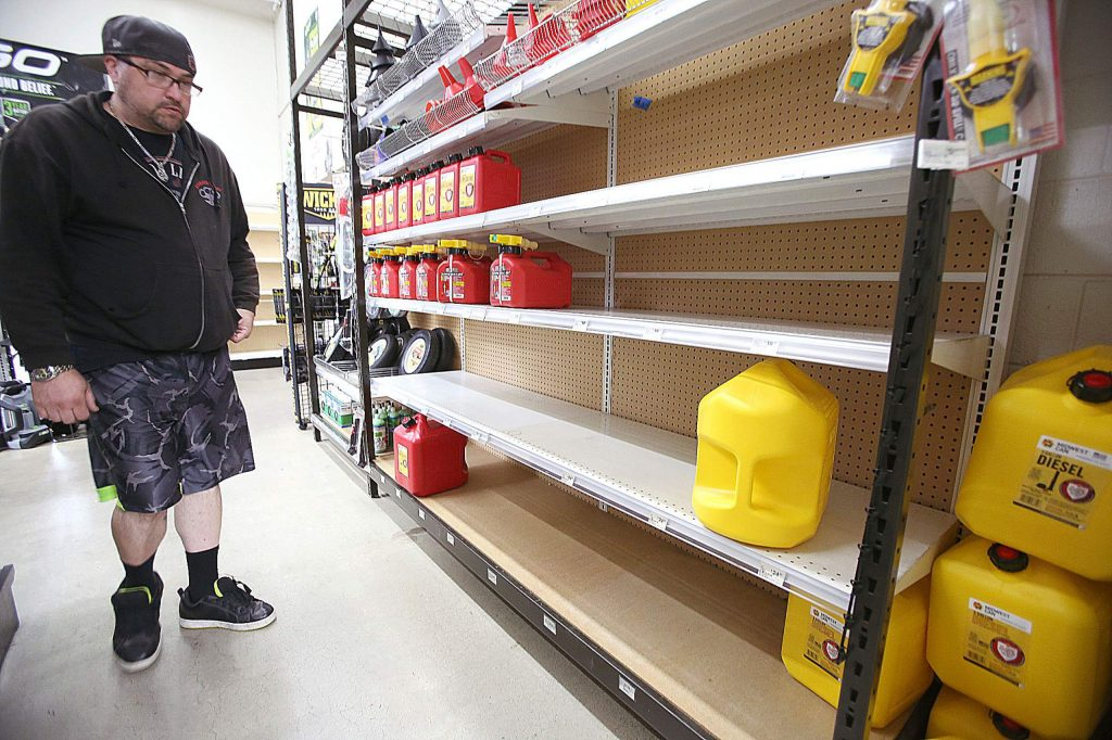 Grass Valley's Dionicio Torres takes in the gas can selection before taking the last 5 gallon gas can on the shelves at B&C Ace Home & Garden Center in the Brunswick Basin Tuesday in preparation of Wednesday's planned public safety power shutdown.