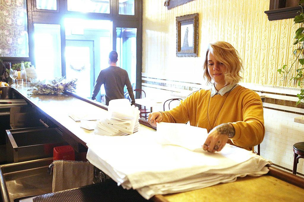 Watershed at The Owl hostess McKenzie Grandas folds cloth napkins while waiting for customers during a particularly slow Wednesday on Mill Street in downtown Grass Valley.