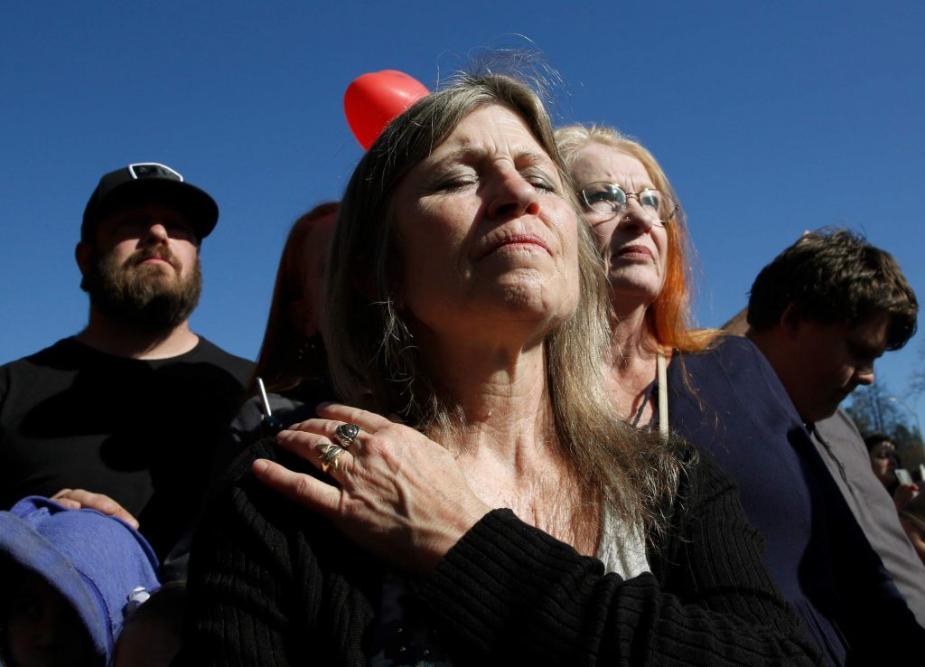 Tami Neves closes her eyes during ceremonies of the one year anniversary of the Camp Fire, held in Paradise Friday.. Neves lost her business in the fire and other family members lost their homes