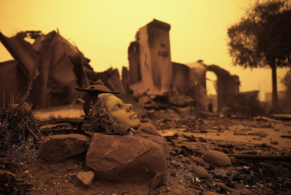 FILE - In this Nov. 9, 2018, file photo, a piece of art sits outside the burned remains of a home destroyed by the Camp Fire in Paradise, Calif. In the year since the fire, crews have removed more than 3.66 million tons of debris, twice the amount that was removed from the World Trade Center site following the 9/11 terrorist attacks. (AP Photo/Rich Pedroncelli, File)