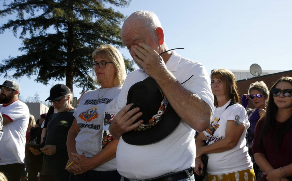 Mike Greer wipes his eyes during the 85 seconds of silence honoring the 85 people who died in last year's Camp Fire during ceremonies in Paradise Friday.