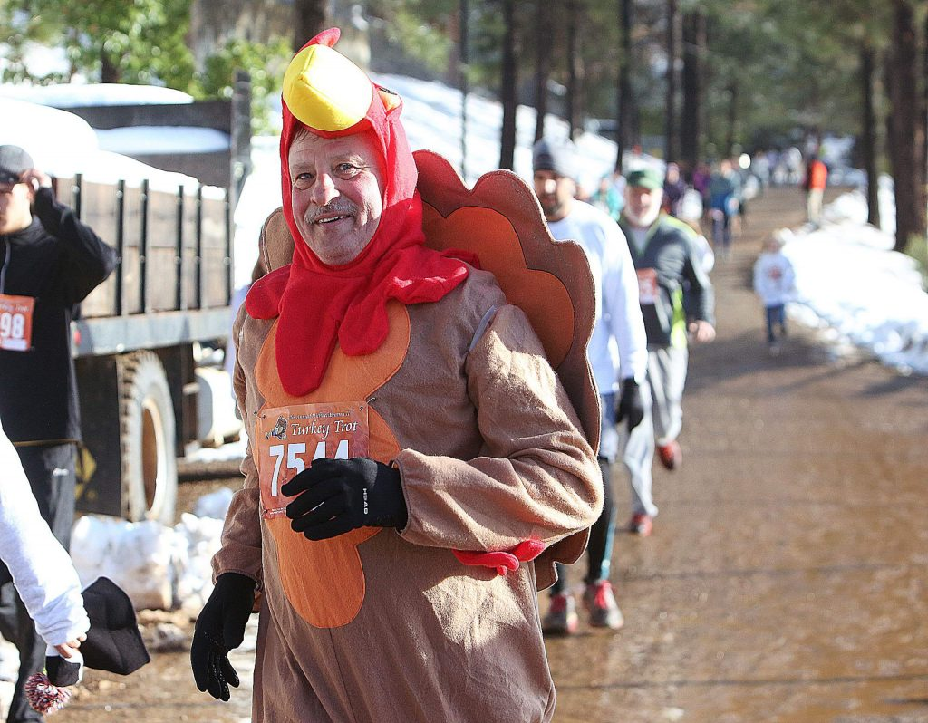 Turkey Trot runner Ray Clark smiles as he rounds the corner for the finish line during Thursday's annual run at NU.