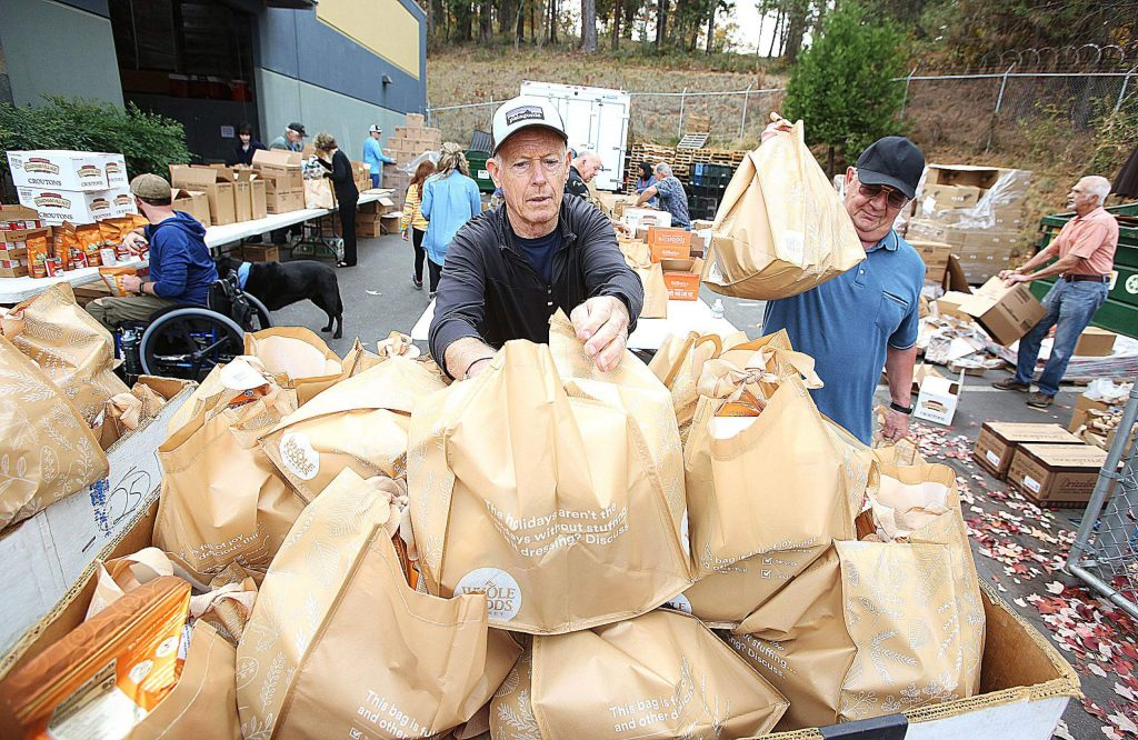 Food Bank of Nevada County volunteers Mike Cartan, center, and Mike Napolitana stack stocked holiday food bags onto pallets Tuesday morning at the Food Bank of Nevada County's property off Railroad Avenue. About 40 volunteers came together to help organize, sort, and prep the more than 650 food bags for their annual holiday distribution set for Thursday.