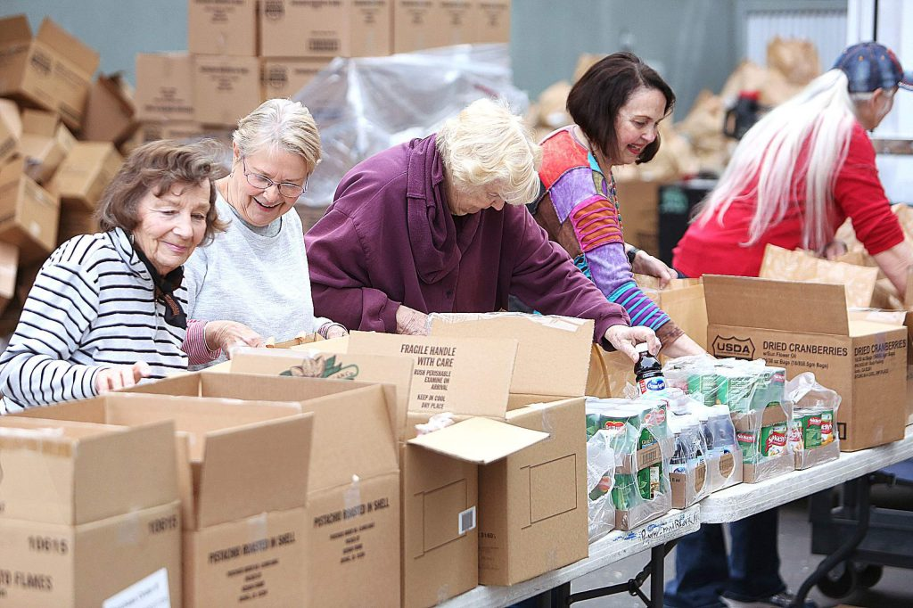 A line of volunteers helps fill holiday food bags Tuesday morning at Food Bank of Nevada County in Grass Valley.