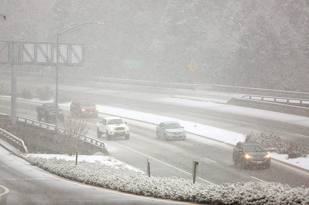 Vehicles navigate the snow covered roadways Tuesday afternoon along the Golden Center Freeway.