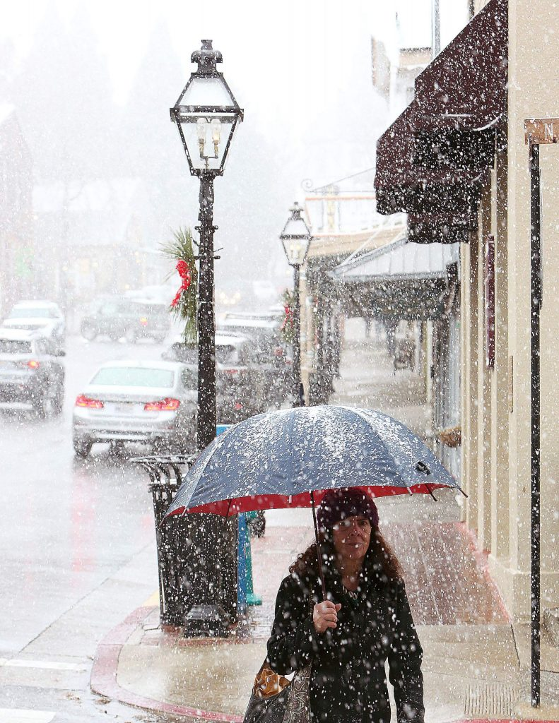 Nevada City's Dancing Water Deerfield shields herself from the snow with her umbrella as she crosses Pine Street in downtown Nevada City Tuesday afternoon.
