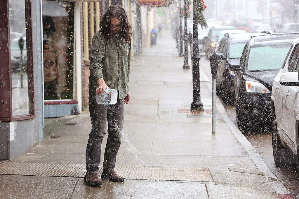 Fur Traders worker Chris Hammond throws some salt onto the sidewalk in front of the Broad Street store in Nevada City to help increase traction for pedestrians.