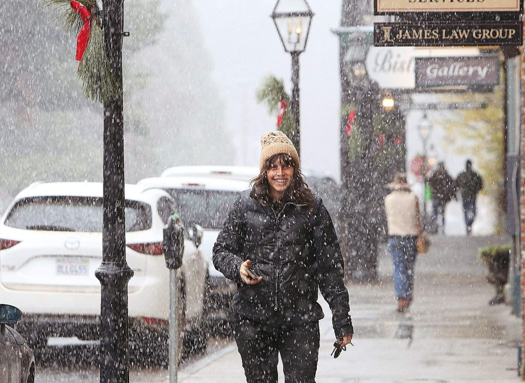 Nevada City's Hollie Dilley smiles as she walks along Broad Street during Tuesday afternoon's snow showers.