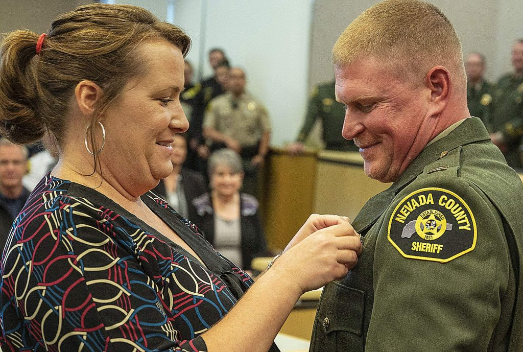 Miranda Brown, left, pinned the captain's badge on her husband Sam Brown.