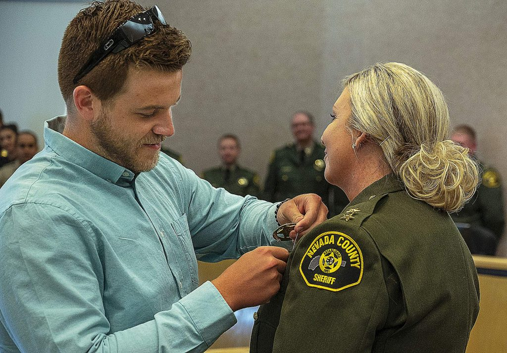 New Undersheriff Alicia Burget, right, had her youngest son Chase Milhous pin the badge on her.