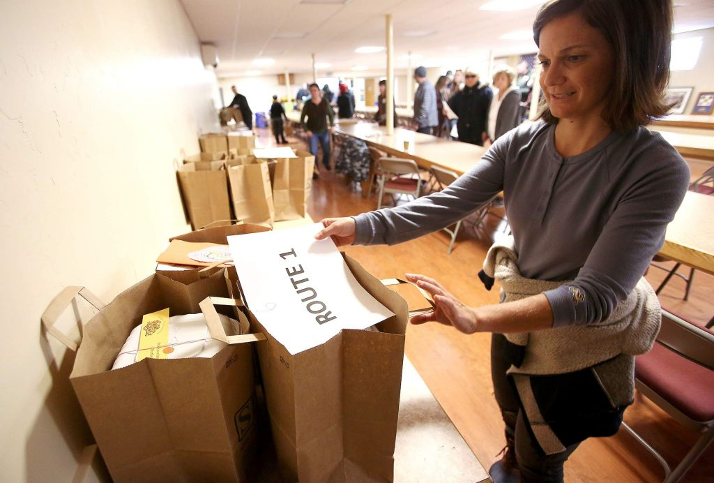 Volunteer Claire Morgan distributes bags full of Thanksgiving meals that will be delivered to different Nevada County households Thursday morning in the basement of the Grass Valley Veterans Memorial Building.