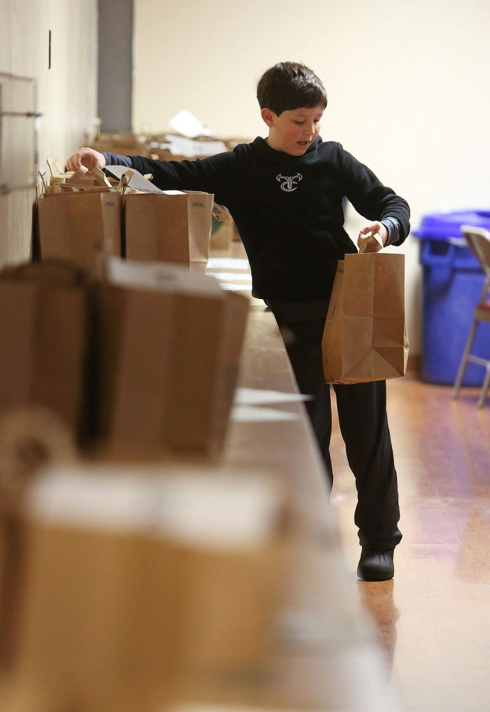 Ten year old Josh Kelso helps hand the Thanks to Give meal bags off to the delivery drivers that will take the Thanksgiving dinners to households across western Nevada County.