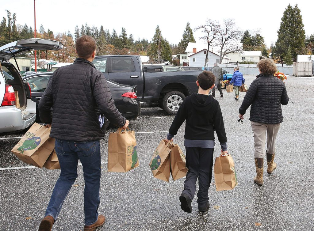 Volunteers carry the Thanks to Give meal bags to vehicles to be delivered to Nevada County households.