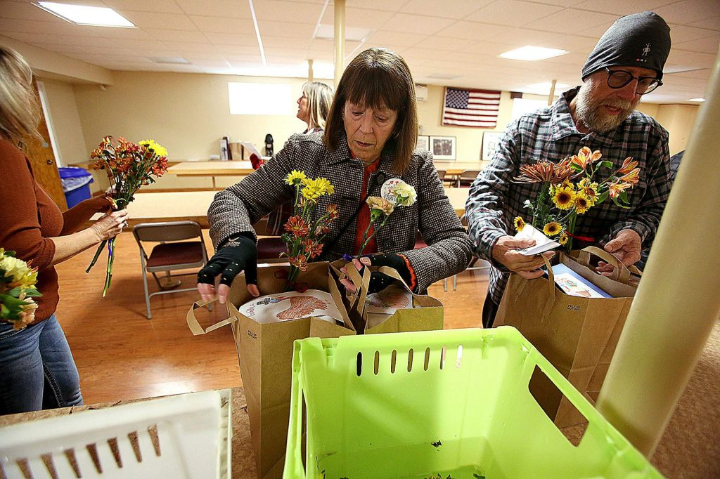 Volunteers pack Thanks to Give food bags with bouquets of flowers to go along with the deliveries.