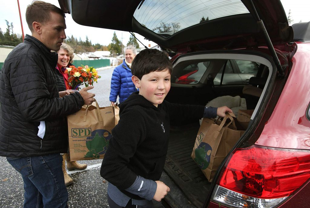 Ten year old Josh Kelso helps load the Thanks to Give meal bags in the vehicles of delivery drivers that will take the Thanksgiving dinners to households across western Nevada County.