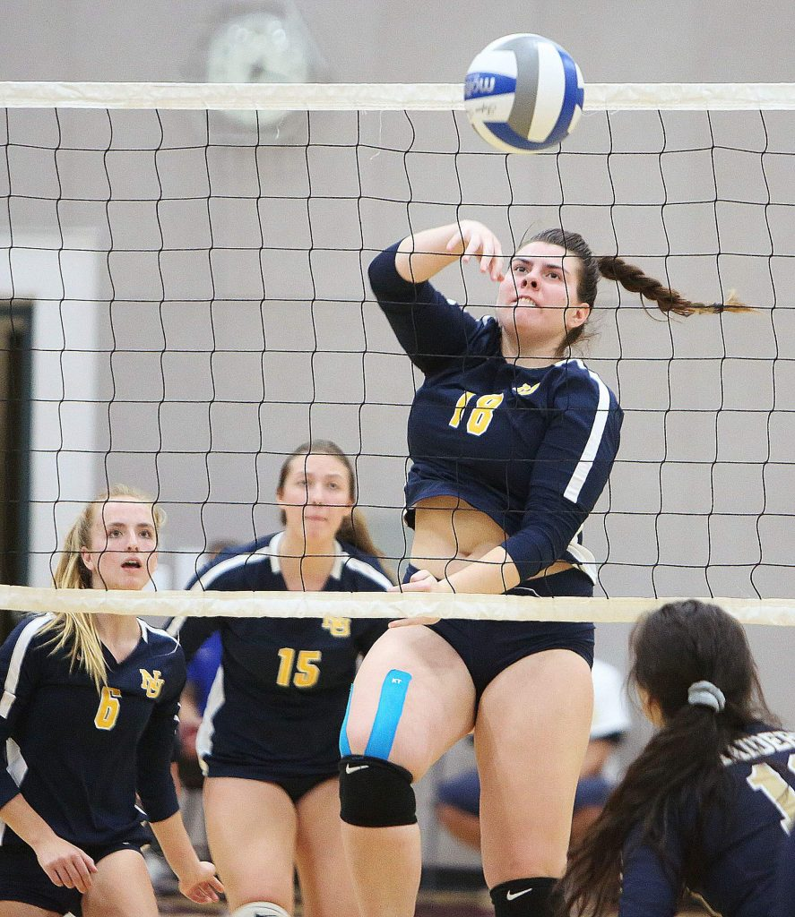 Nevada Union junior Ashlyn Franssen (18) spikes the ball over the net for the Miners.