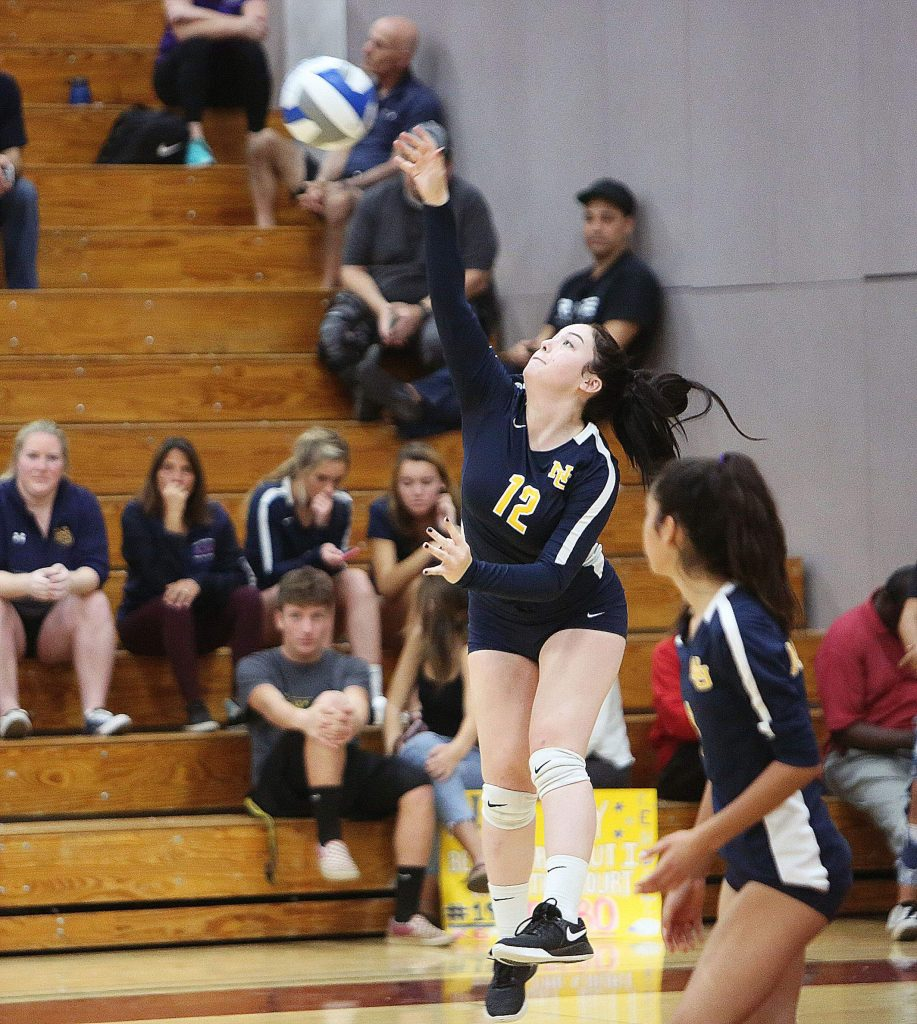 Kiana Spillner (12) sends a serve over the net for the Miners.