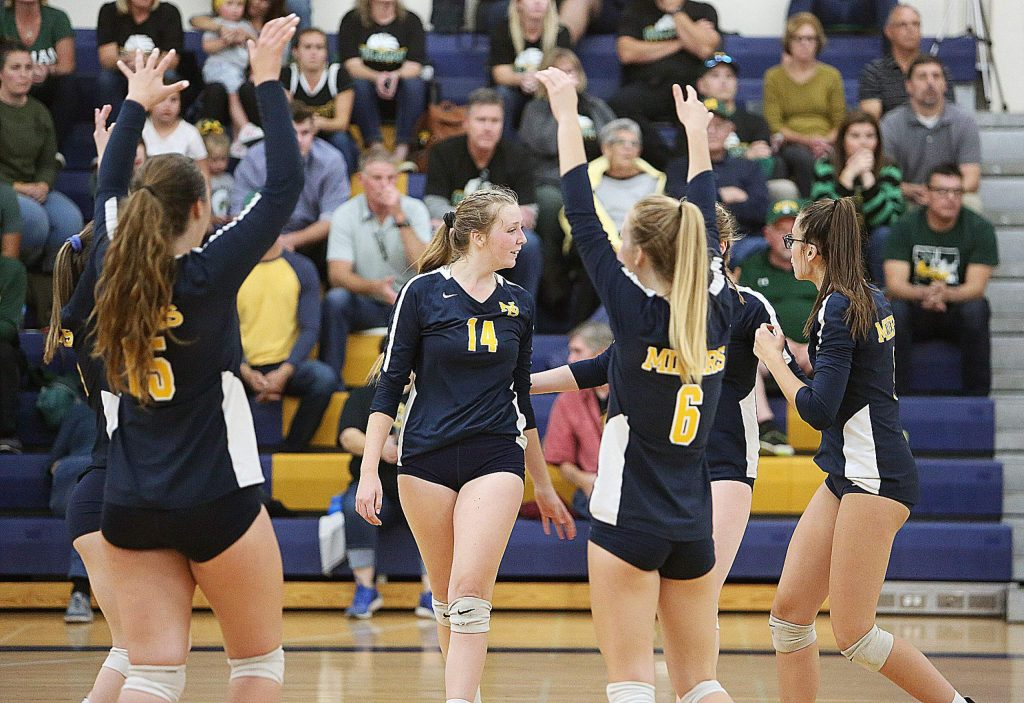 The Lady Miners celebrate a point against the Yellowjackets.