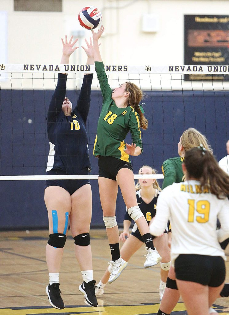 Ashlyn Franssen (18) looks to defend against Hilmar's Emma Martin (18) at the net.