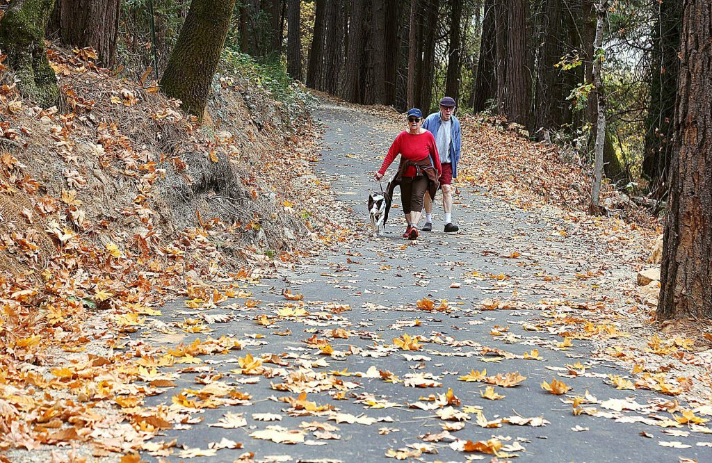 A Nevada City couple walk their dog along a leaf-studded Wolf Creek Trail Wednesday afternoon in Grass Valley. The National Weather Service is warning of the potential of fire weather on Tuesday.