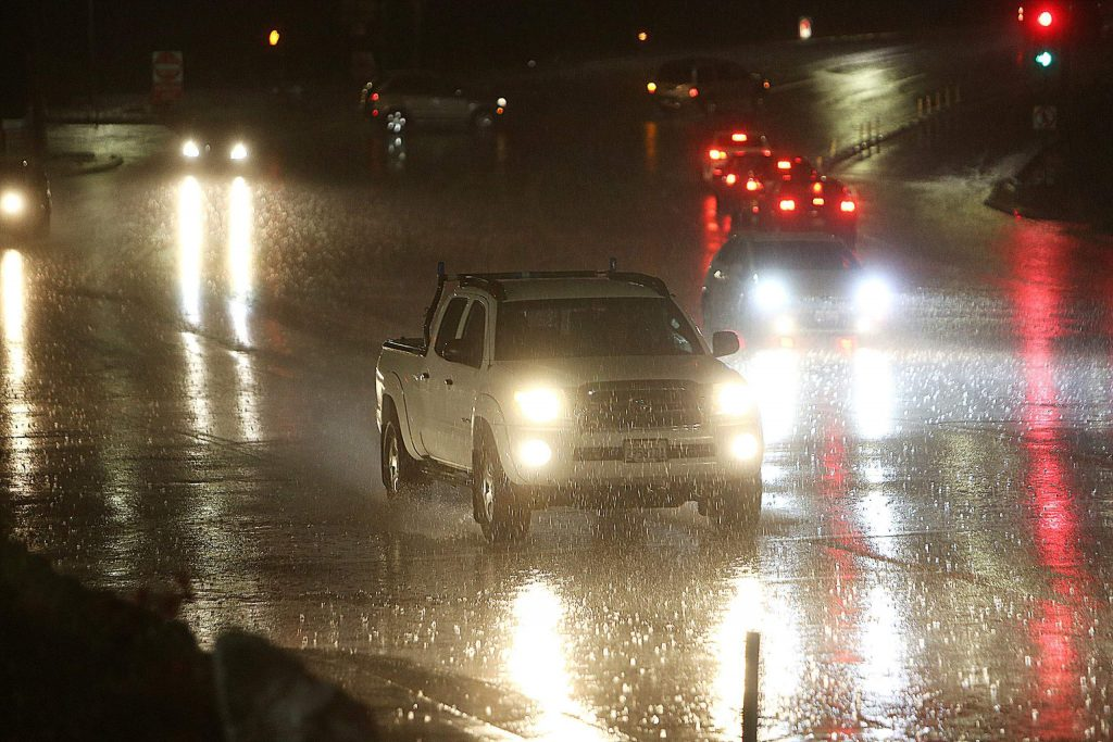 Vehicles navigate the rain laden intersection of Brunswick Road at Sutton Way during Tuesday evening's storm. A rain gauge showed .34 inches of rain fell near the Nevada County Airport, while the streets of Nevada City were covered in hail.