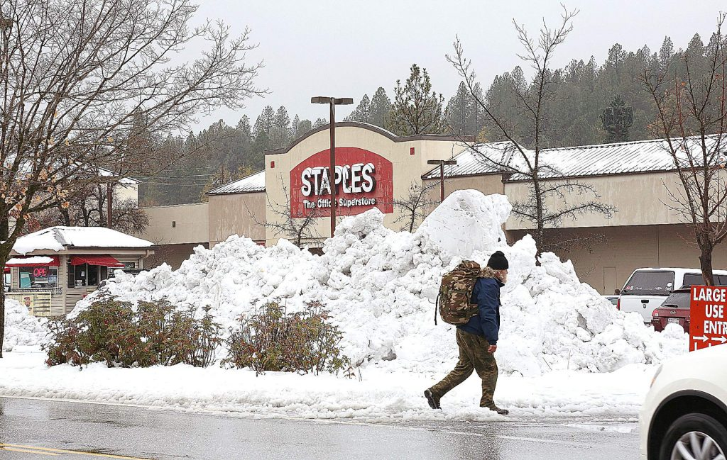 A pedestrian walks in front of a large pile of snow plowed in the parking lot of the Glenbrook Plaza following Tuesday evening's snow storm.