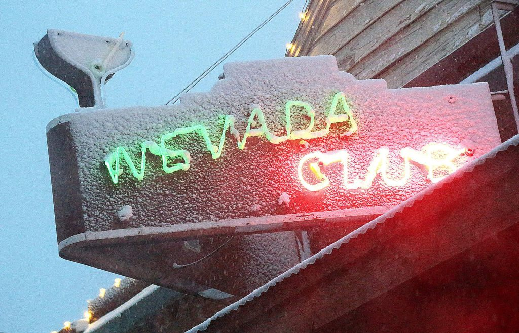 The Nevada Club sign looks a little frosty Tuesday evening as snow falls to as low as 1,500 feet in elevation.
