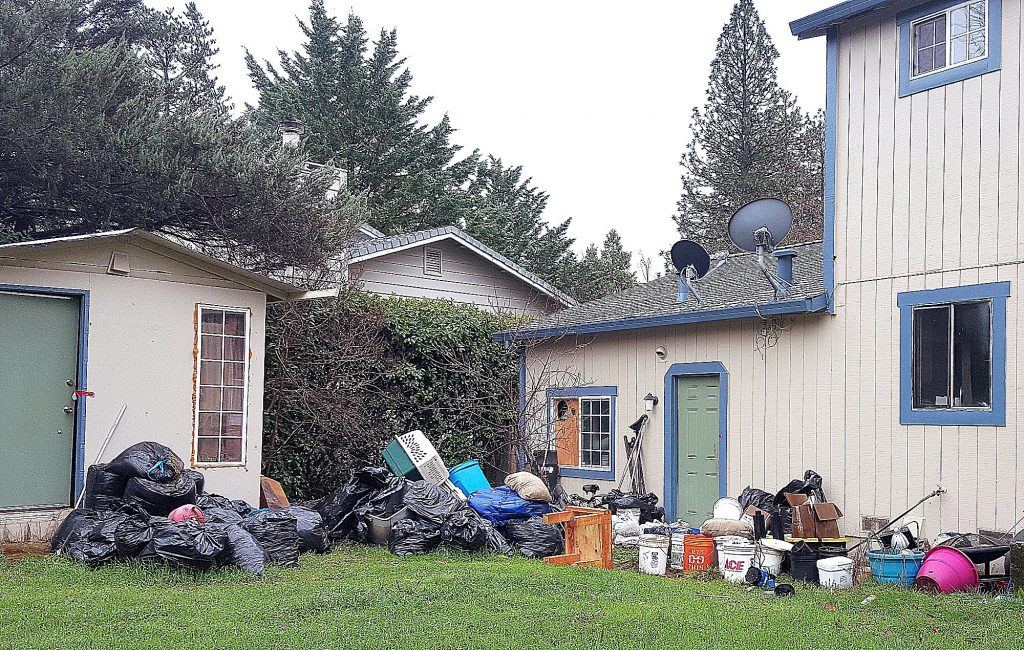 Garbage litters the back yard of a Cypress Hill residence where authorities allegedly located drug manufacturing equipment.
