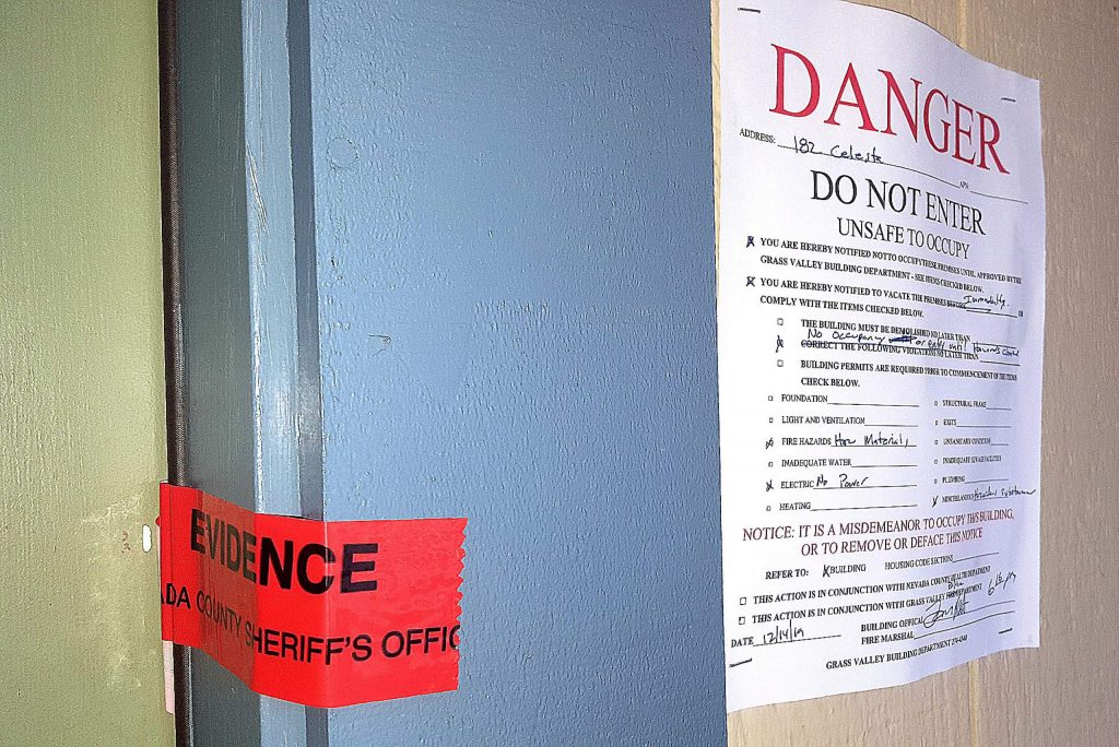Evidence tape seals the front door, and a danger sign is posted, at  a residence on Celesta Drive where a cannabis extraction lab reportedly was found.