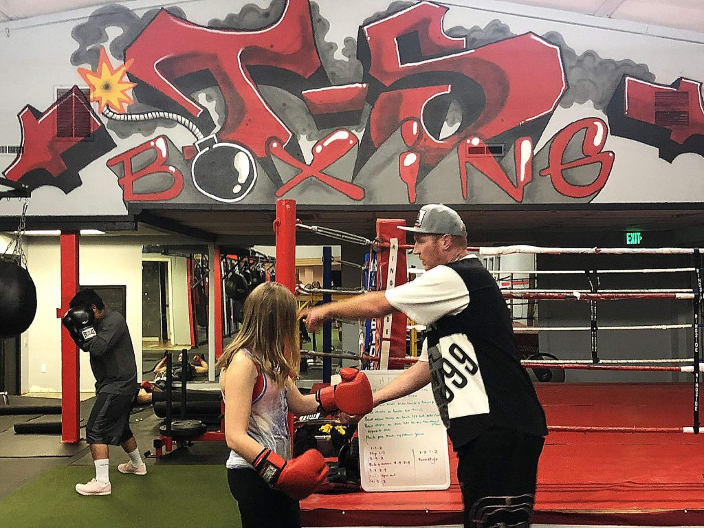 Brian Scott, right, helps a young student with her gloves. When Scott rebooted T-5 Boxing 18 months ago, his goal was to offer a place for young people to come and channel their anger in a positive and productive manner.