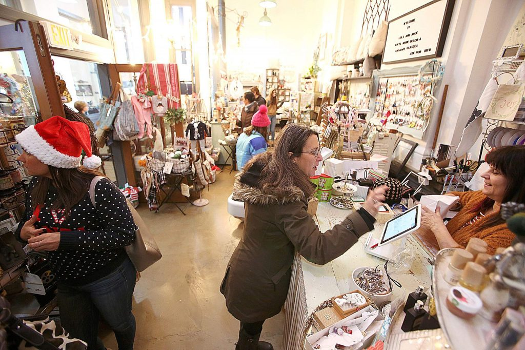 Grass Valley and Nevada City were abuzz on the last Christmas shopping day of the year Tuesday, including at Lola and Jack's Gifts, Home Decor & Creative Classes inside of the old Nevada County Bank building on Mill Street. Vendors such as Karen Lian, right, were busy much of the day helping folks with their last minute gift shopping.
