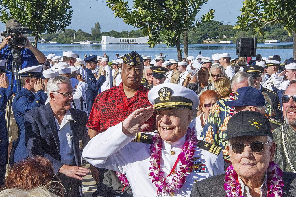 Arizona survivor, Louis Conter, center, salutes as he leaves the National Pearl Harbor Remembrance Day ceremony at the Arizona Memorial in Honolulu, Hawaii.    Survivors gathered Thursday at the site of the Japanese attack on Pearl Harbor to remember fellow servicemen killed in the early morning raid 76 years ago, paying homage to the thousands who died with a solemn ceremony marking the surprise bombing raid that plunged the U.S. into World War II. (Craig T. Kojima /The Star-Advertiser via AP, Pool)