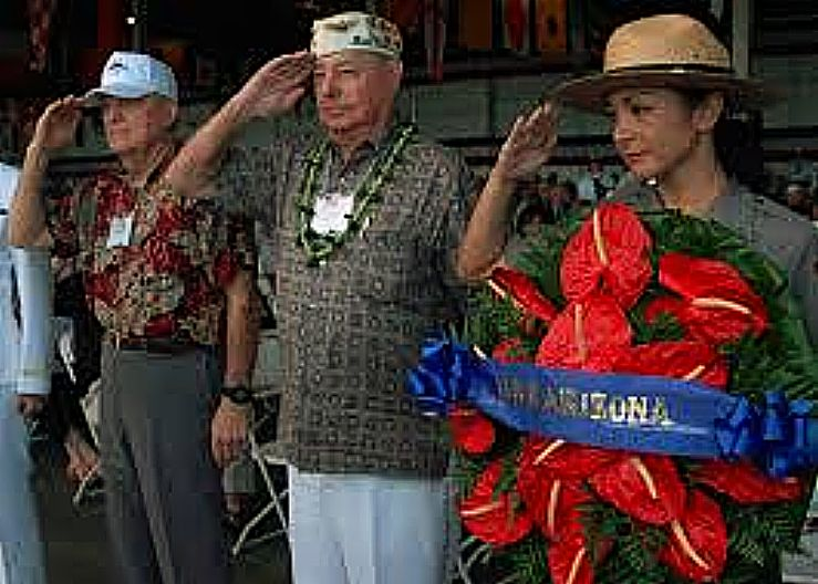 """Pearl Harbor survivor Lou Conter, center, and National Park Service Ranger Nancy Reames renders a salute before hanging a wreath in honor of USS Arizona (BB 39) during a joint U.S. Navy/National Park Service ceremony commemorating the 67th anniversary of the attack on Pearl Harbor. The theme of this year's commemoration, """"Pacific War Memories: The Heroic Response to Pearl Harbor,"""" emphasizes the brave efforts of those who fought at sea, on land and in the air to turn the tide in the Pacific. More than 2,000 distinguished guests and the general public joined service members, Pearl Harbor survivors and their families and friends for the annual observance. (U.S. Navy photo by Mass Communication Specialist 1st Class Sarah Murphy/Released)"""