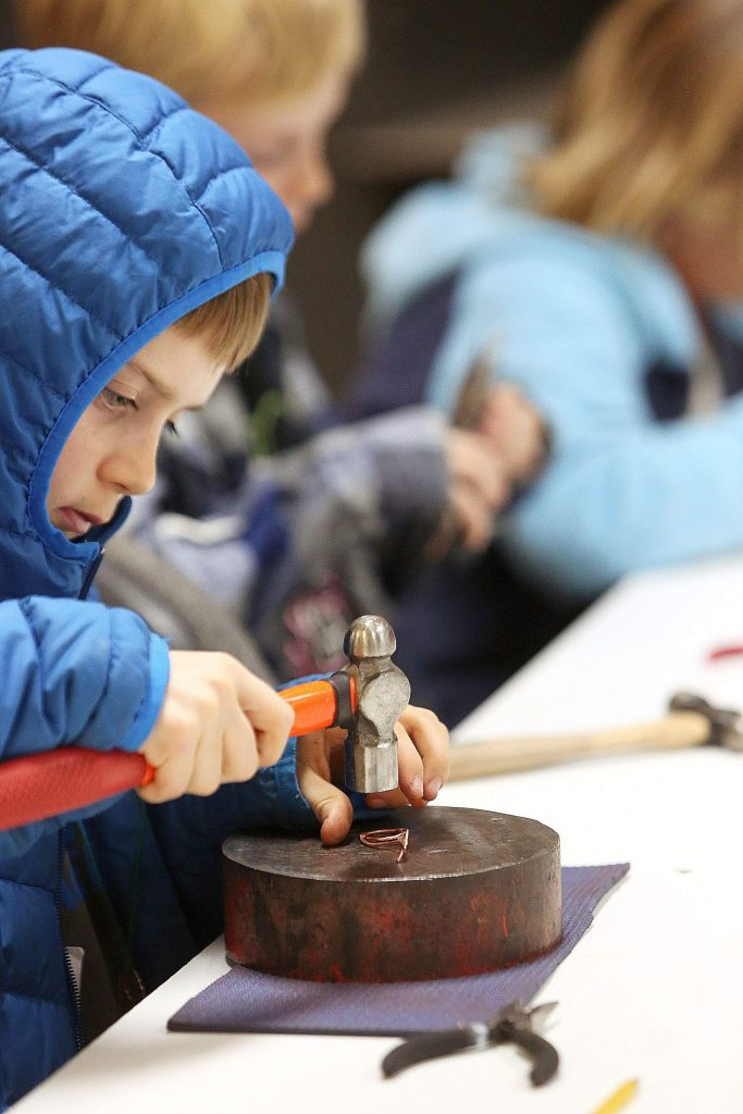 Dylan Krutzman uses a hammer and an anvil to help form his copper creations Tuesday at the Curious Forge maker space.