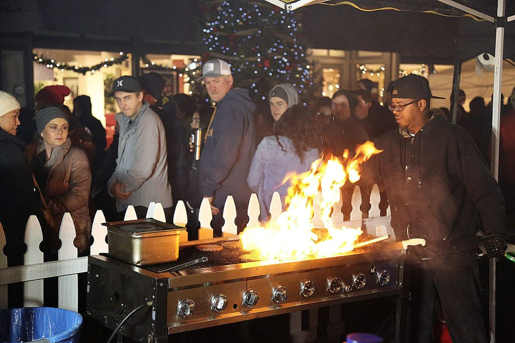 Cooks from Kenny Concessions make their charbroiled burgers amidst a flash of flame and smoke on Mill Street following the tree lighting ceremony Friday night.