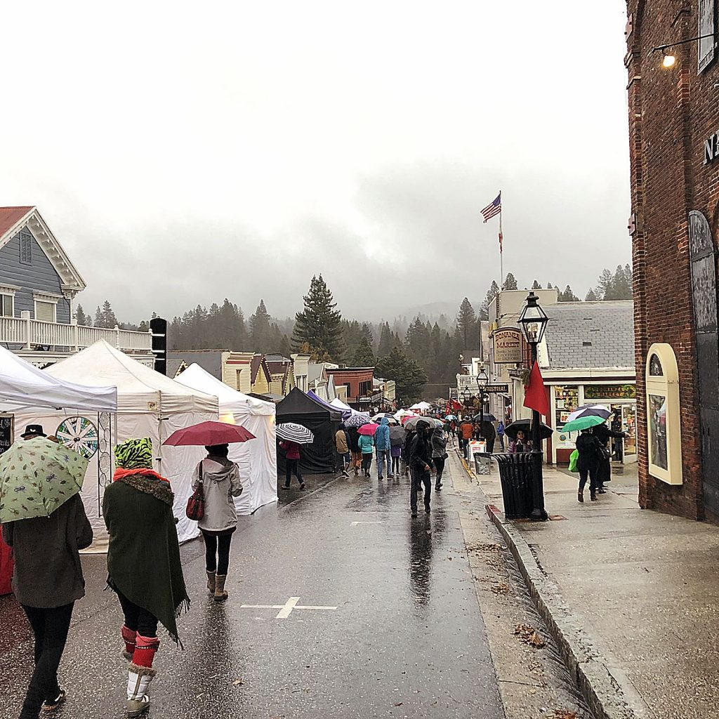 Undettered by the rain, Victorian Christmas attendees stroll through Nevada City, appreciating the celebratory cheer.
