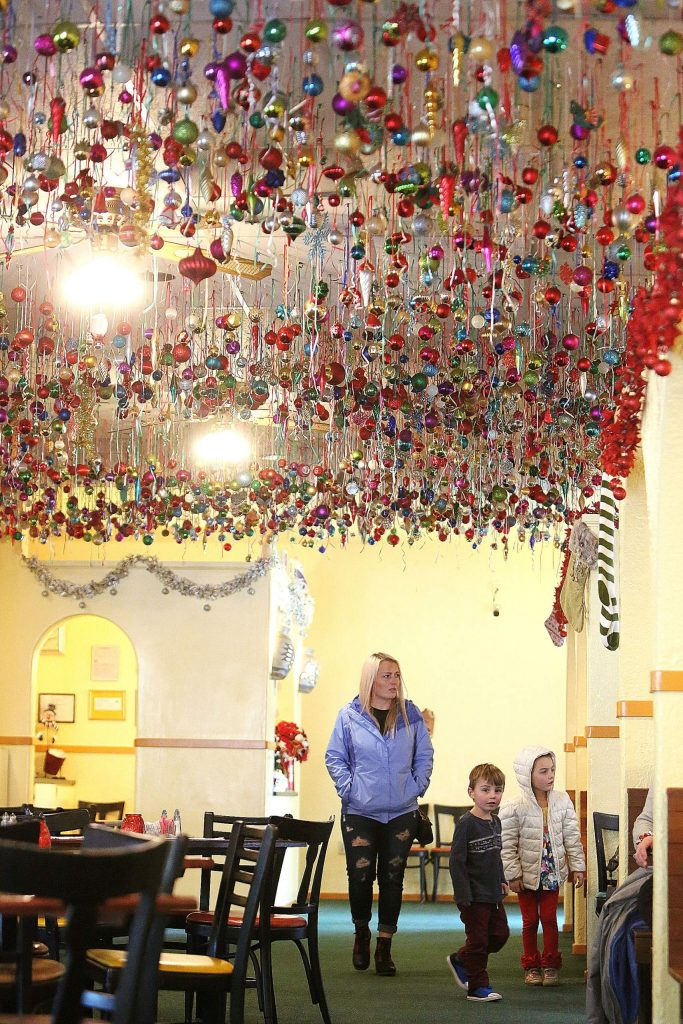 Customers walk under the massive display of Christmas ornaments while dining at Margaritas in Grass Valley Tuesday.