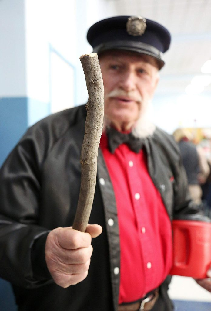Joe Kasza holds a stick in one hand and a donation bin in the other while participating in Friday morning's Donation Day parade through the streets of downtown Grass Valley. Donation Day tradition, which dates back to the 1880s, originally asked for participants to bring a stick and a potato. The stick for burning in the stove, and a potato for cooking.