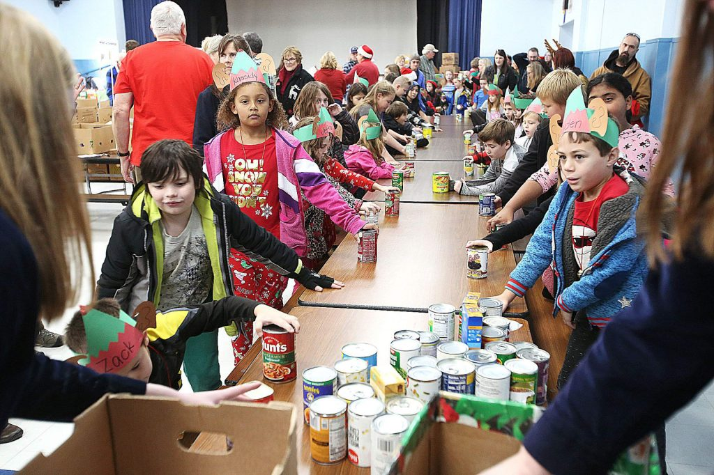 Youngsters from area schools bring in their canned food items while a pair of Nevada Union FFA members box the cans to be sorted through.