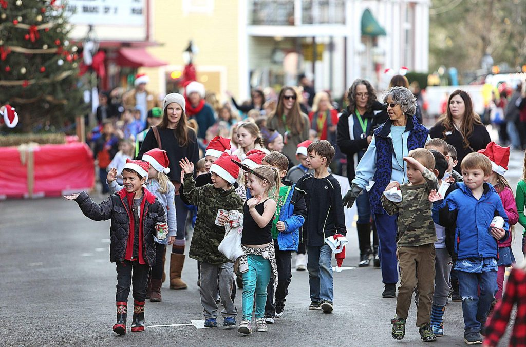 Youngsters wearing festive holiday attire wave and carry their canned goods for donation during Friday morning's Donation Day parade.
