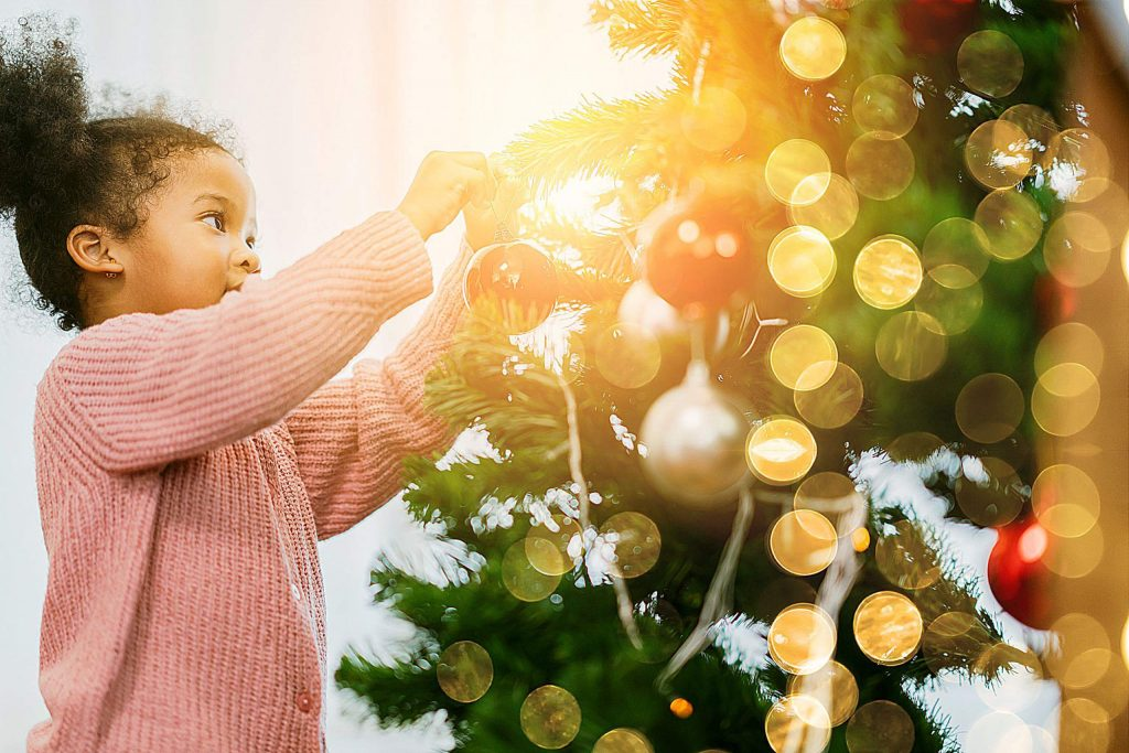 african female kid arrange decorate christmas tree with fun and cheerful christmas festive ideas concept