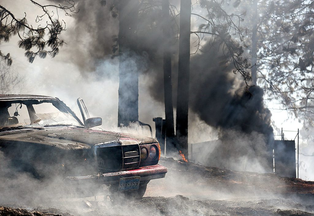 45) Black smoke billows from a container shed that caught fire during an incident off of Venus Court in August. A vehicle and a motor home were also destroyed during the five-acre fire, but the residence on the property was saved.