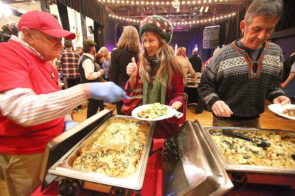 KVMR's Melissa Seibold gives the thumbs up of approval while filling her plate during Saturday's Night of Giving at the Miners Foundry. The Hospitality House homeless shelter benefit featured meals such as chicken piccata, Mediterranean quinoa, and roasted veggies with pasta, all prepared by the shelter's culinary program.